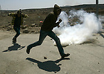 Palestinians take cover from tear gas during clashes at Qusra village near the West Bank city of Nablus on 16 September 2011. Israeli settlers assaulted the village Friday morning, leading to clashes with Israeli forces injuring 11 Palestinians. After the settlers were removed by Israeli police, Israeli forces raided Qusra village injuring another six villagers with rubber bullets, Palestinian sources said. Photo by Wagdi Eshtayah