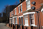 Red brick terraced house with TV satellite dishes, central Ipswich, Suffolk, England