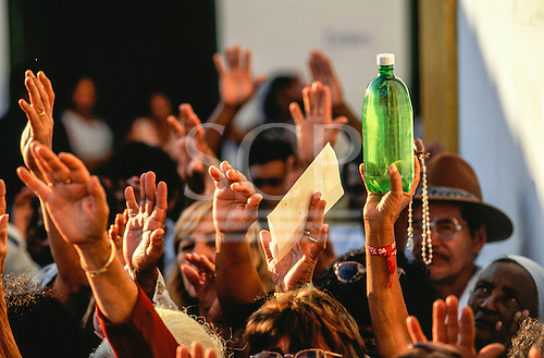 Porto Seguro, Brazil. Hands of pilgrims at a religious festival with rosary and bottle of holy water in street outside a church.