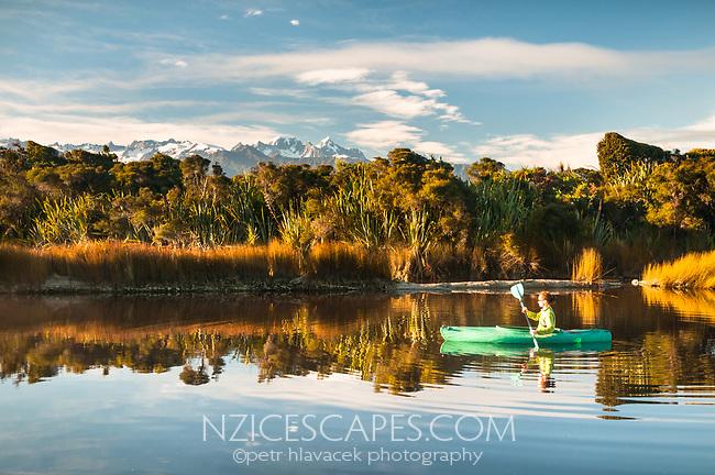 Kayaking in coastal lagoon near Okarito with views of Southern Alps, Westland Tai Poutini National Park, West Coast, UNESCO World Heritage Area, New Zealand