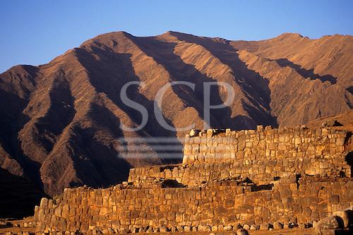 Chinchero, Peru. Inca masonry stone walls with deeply eroded mountains behind.