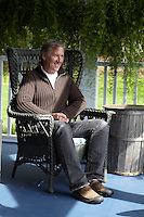 James Huniford sitting in one of his high back wicker chairs on the poch of his family home