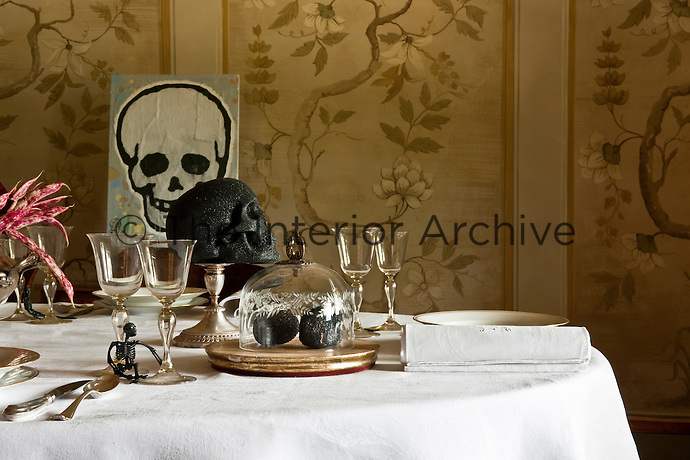 A pair of truffles presented under an antique glass bell on a laid table with a skull centrepiece