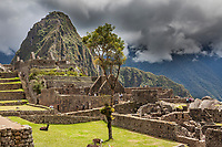 "Huayanapichu (young mountain) in the distance at Machu Picchu, the ancient ""lost city of the Incas"",  built about 1400 CA. Discovered by Hiram Bingham in 1911. One of Peru's top tourist destinations."