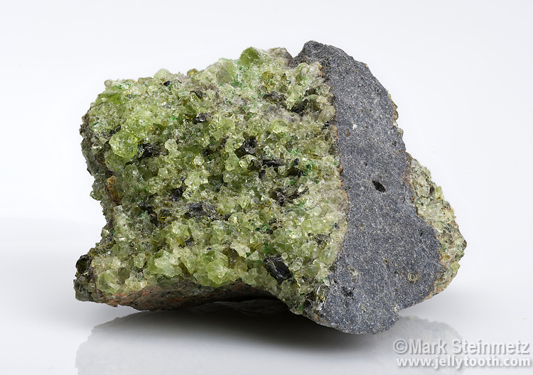 Peridot in vesicular basalt, San Carlos Apache Reservation, Arizona, USA. Peridot is gem-quality olivine, a magnesium iron silicate mineral. Peridot Mesa, located on the San Carlos Apache Indian Reservation east of Globe in Gila County, is the most productive locality for peridot in the world.