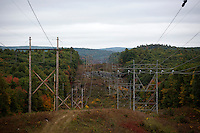 Powerlines and poles stand in a cut through the forest off of State Highway 202 near New Salem, Massachusetts, USA.