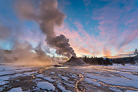Yellowstone National Park, Wyoming:<br /> Steam plume venting from Castle Geyser with dawn clouds in the sky. Upper Geyser Basin