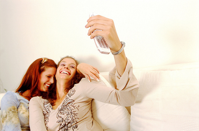 Beaute, deux femmes se photographiant avec un telephone portable *** Two women photographing themselves with a mobile phone, Female Beauty