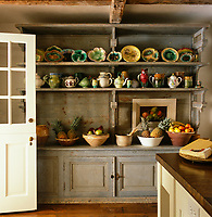 A 19th century French dresser found in a bakery in the Dordogne displays a collection of earthenware and majolica against one wall of this rustic kitchen