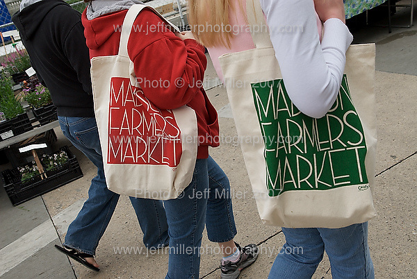 Women carrying a market bags purchase walk past vendor stands during the Dane County Farmers' Market in downtown Madison, Wis. on May 26, 2007..Photo © Jeff Miller 2007 - all rights reserved.www.jeffmillerphotography.com  ?  608-250-2374.Date:  05/07    File#:   D200 digital camera frame 4294