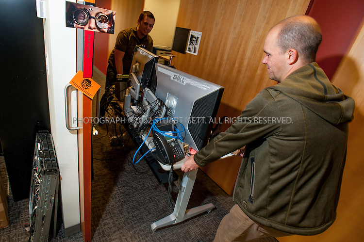 8/2/2012--Bellevue, WA, USA..Jeff Bellinghausen (right) moves a desk into an office for an employee at gaming software maker Valve...The office is set up as a 'boss less' office that is fluid and non-hierarchical. Desks come with wheels so that they can be easily moved and reconfigured to create new work spaces for new projects. The desks can also be raised or lowered for comfort or to create a standing work space...©2012 Stuart Isett. All rights reserved.