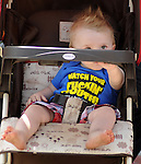 A baby wears a Tee shirt with a message on the sidelines of the Saugerties July 4th Parade on Main Street in Saugerties, NY on Monday, July 4, 2011. Photo by Jim Peppler. Copyright © Jim Peppler 2011.