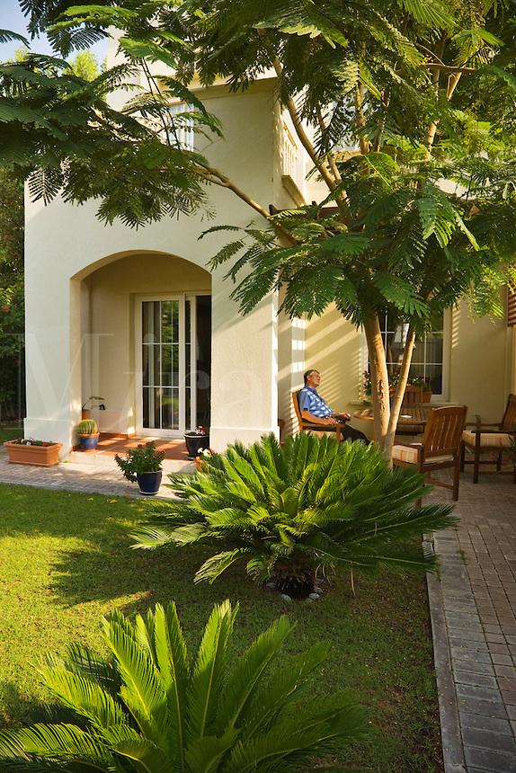 Dubai.  Man relaxes in the garden of his villa.