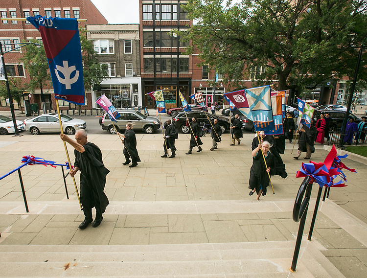 Banner and flag carriers battle the blustery winds as they arrive at the St. Vincent de Paul Parish Church Thursday, Aug. 31, 2017, during the procession to the annual Academic Convocation. (DePaul University/Jamie Moncrief)