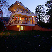 The elongated form of the house, with its curvaceous deck-like terraces, thrusts like the bow of a ship into the garden