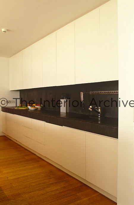 View of a wall of built-in kitchen units in the open-plan kitchen