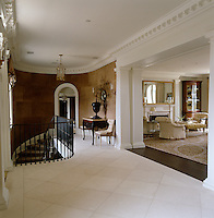 Laid on the diagonal, a pale limestone floor brings  lightness and freshness to the hall
