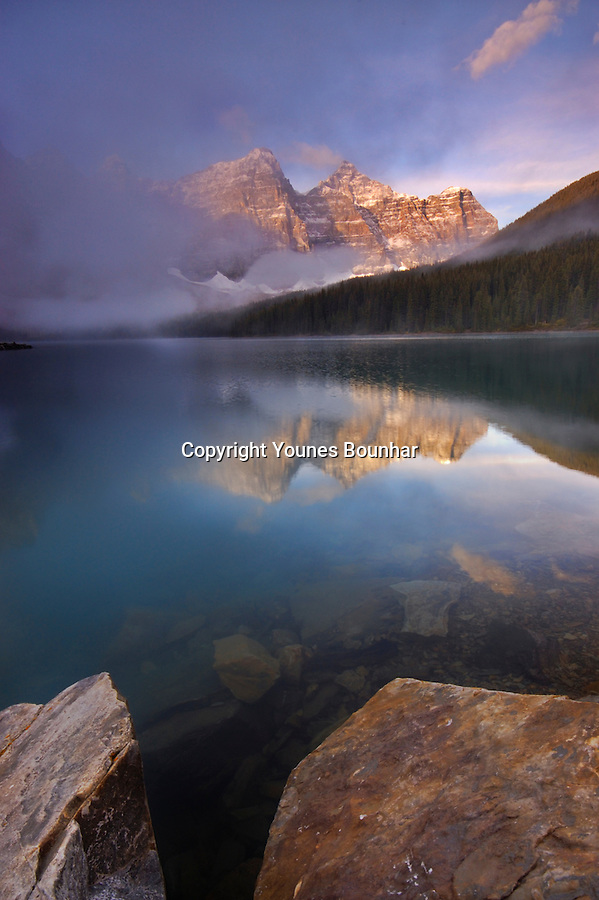Fog rises as valley of ten peaks is reflected on the turquoise surface of beautiful Moraine Lake at sunrise, with rocks in the foreground