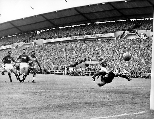 The Brazilian striker Vava (l). scores between two USSR opponents. USSR-keeper Lev Yaschin (r) dives in vain for the ball. Brazil wins the game in the world championship in Sweden on 15.06.1958 before 51,000 spectators in the Goeteborger Nya Ullevi stadium in group play against the USSR by a score of  2:0.