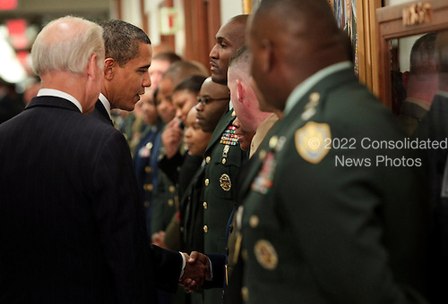 Arlington, VA - January 28, 2009 -- United States President Barack Obama (R) and Vice President Joe Biden (L) greet service men and women after a meeting at the Pentagon, Wednesday, January 28, 2009 in Virginia.  President Barack Obama and Vice President Joe Biden met with Secretary of Defense Robert Gates and the Joint Chiefs of Staff to discuss America's military situation in the world..Credit: Brendan Smialowski - Pool via CNP