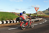 MAURITIUS, a boy gets a ride home from school on his faters motorbike