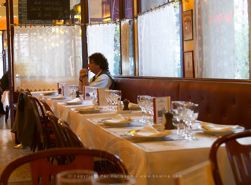 The classic restaurant brasserie Bolingrin with tables set with glasses and linen napkins and table cloth, knives and forks, salt shaker and pepper, a man sitting alone at the far table waiting for someone another person, Reims, Champagne, Marne, Ardennes, France, low light grainy grain