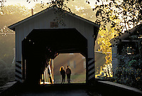 Couple strolling through a covered bridge. Couple. Strasburg Pennsylvania USA Lancaster County.