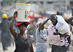 A survivor of the January 12 earthquake carries water in the Belair neighborhood of Port-au-Prince, Haiti