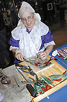 Sentinel/Dan Irving.Stained glass artist Florence Kornoelje of Grandville works on a tulip-themed piece in her booth at the Dutch Marktplaats Friday afternoon at the Holland Civic Center..(5/12/06)
