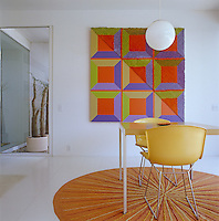 A large artwork hangs on the wall in the open-plan living/dining area