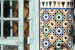 An old wooden door and decorative tiles in the Bahia Palace in Marrakesh, Morocco.
