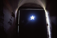 Light creeps into a WWII Bunker through a star-shaped look-out and around the edges of the door.