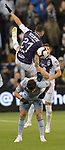 Miguel Layun (top) of C.F Monterrey leaps and falls over Felipe Gutierrez of Sporting KC during their CONCACAF Champions League semifinal soccer game on April 11, 2019 at Children's Mercy Park in Kansas City, Kansas.  Photo by TIM VIZER/AFP