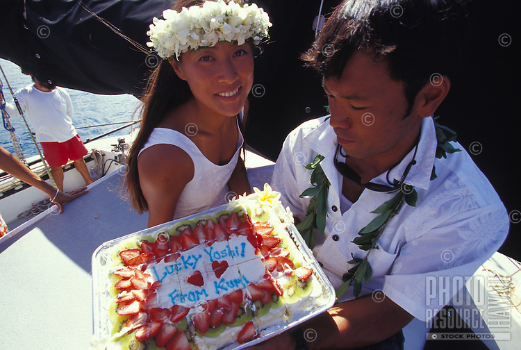 Couple with wedding cake getting married on a boat off Haleiwa, on the North Shore of Oahu, Hawaii