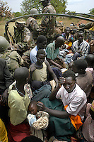 Villagers catch a ride in a troop truck north of Lira to get to food. Because of the presence of the LRA they could not go to their fields to pick food. Troops took them to where they could get some food. The truck was in President Yoweri Museveni's convoy into the bush as her toured the area following an attack on a camp for internally displaced people on Saturday where more than 190 people were killed. (Rick D'Elia) Feb 24, 2004.