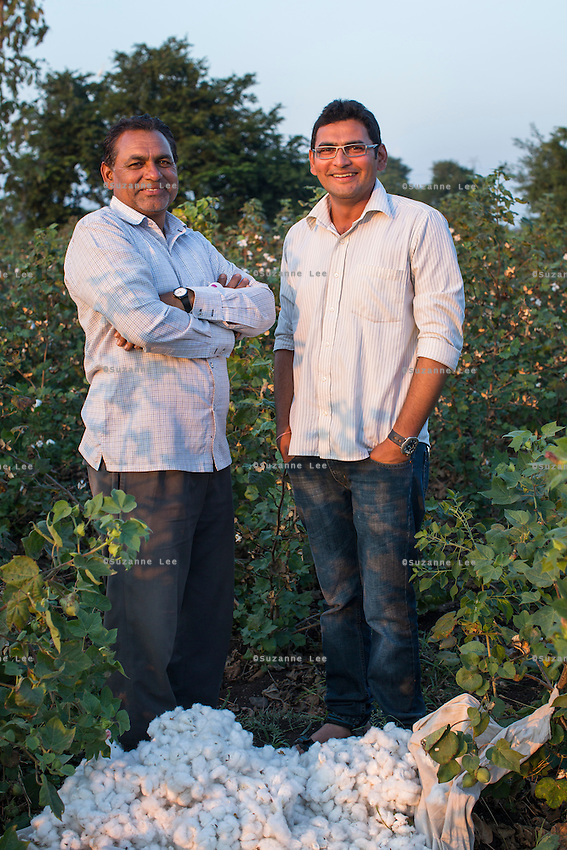 Two generations of cotton farmers, Jagadish Dhannanlal Patidar, 54, a farmer leader, stands in a Fairtrade cotton farm with his son, Amit Patidar (who had studied Advertising in college) in Karhi, Khargone, Madhya Pradesh, India on 12 November 2014. Jagdish says that he has a lower turnover of workers because they are fairly paid, and Amit wants to continue farming Fairtrade cotton while putting his advertising knowledge into growing the business. He uses the internet a lot to get weather reports which help him with farming decisions. Photo by Suzanne Lee for Fairtrade