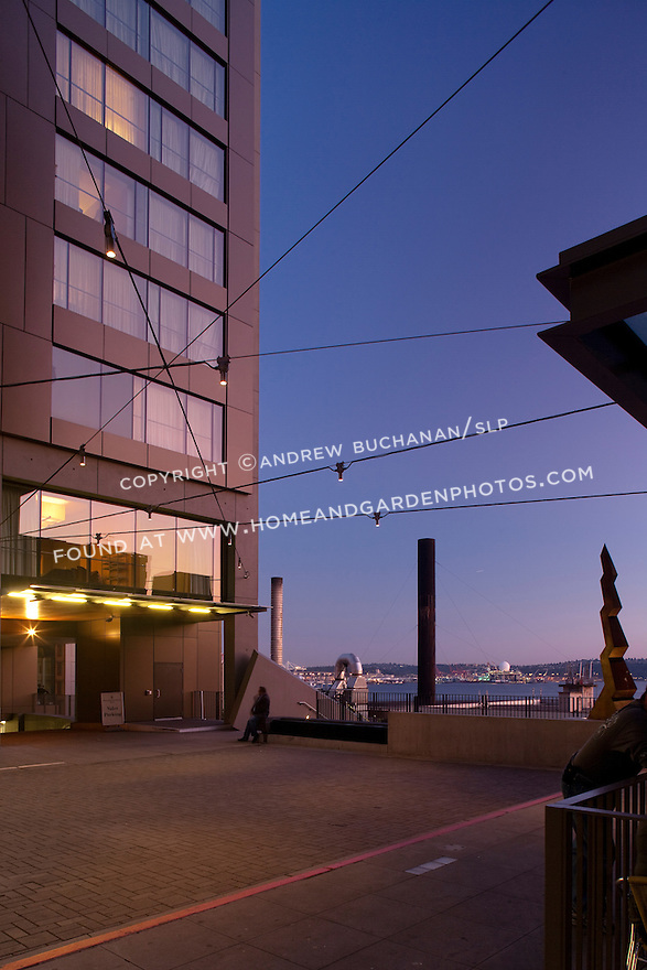 With Elliott Bay in the background, lights illuminate a downtown Seattle plaza on a summer night.