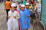 A group of young Muslim boys wearing traditional colourful kurta tops and prayer caps in Old Dhaka.