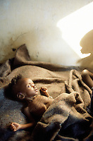 Angola. Cuando Cubango. Mavinga. Young girl, malnourished child, lays on a bed in a hospital run by MSF (M?decins Sans Frontires) Switzerland. The shadow on the wall is her brother who also suffers from malnutrition. © 2002 Didier Ruef