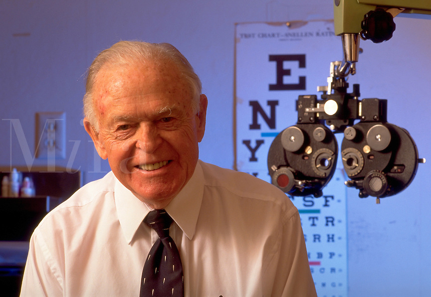 a very old eye doctor who has kept working way past his retirement age. this portrait is taken in his office with some of his old eye exam equipment and an old eye chart. Dr. Stayer. United States doctor's office.