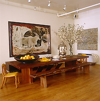 The immense dining table, which seats 24, is 15 feet long and is made from a single piece of Indonesian mahoni with Peter Beard's photograph Ele and Eland on the wall behind