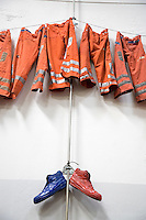Switzerland. Canton Ticino. Bellinzona. Officine FFS. Stabilimento Industriale SBB CFF FFS Cargo. Railway workers on strike. Building's occupation. The orange and blue clothes and shoes of the blue collar workers are hanged on the wall. © 2008 Didier Ruef