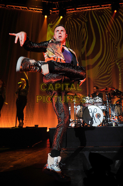 Jake Shears.Scissor Sisters performing live in concert, Camden Roundhouse, London, England. .23rd October 2012.on stage gig performance performing music full length black trousers orange green print jacket dancing mouth open leg foot up funny hands arms funny.CAP/MAR.© Martin Harris/Capital Pictures.