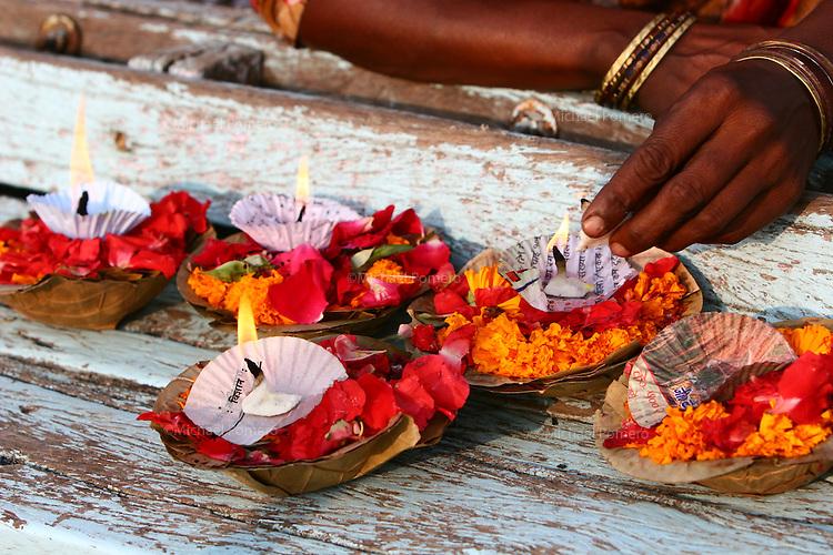 03.11.2007 Varanasi(Uttar Pradesh)<br /> <br /> Women lighting candles of offerings in a boat on Ganga river.<br /> <br /> Femme en train d'allumer des bougies d' offrandes sur un bateau du Gange.