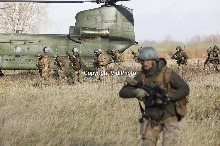 Foto: VidiPhoto<br /> <br /> HEUSDEN - Generale repetitie voor het 12e infanteriebataljon Airassault van de Luchtmobiele Brigade. Vlak voordat ze een maand naar de VS vertrekken voor certificering en het aanscherpen van vaardigheden, moeten ze donderdag in het Brabantse Heusden nog een terroristencel oprollen. In de voormalige Hak-fabriek worden ditmaal geen bonen ingeblikt, maar explosieven geproduceerd. Om de oefening extra ingewikkeld te maken zijn er niet alleen een vijftiental terroristen actief, maar lopen er ook onschuld burgers tussendoor. De zestig aanvallers moeten niet alleen de vijand onschadelijk maken, maar ook de explosieven veilig stellen. De training in Amerika vindt plaats in Fort Hood in Texas.