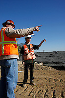 Faten Khabib a geologist with Helenschmidt Geotechnical Inc and Ron Strathman of Quatum Risk Management stand on a large mound of earth near the site of the most recent landslide on Mount Soledad, Friday January 18, 2008.