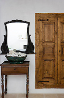 Anurag collects beautiful white stones in the antique Italian bowl in the living room. The mirror is from her family home back in Milan, whilst the little table was found locally