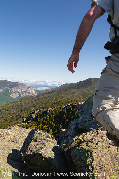 A hiker rock hopping on the summit of Mount Liberty during the summer months in the White Mountains, New Hampshire USA. Franconia Notch State Park is in the valley.