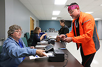NWA Democrat-Gazette/DAVID GOTTSCHALK  Kirk Melo (right) checks in with Vicki Penny, with the Benton County Election Commission, Monday, November 5, 2019, before receiving his ballot to vote in the 2019 Bentonville Annual School Election inside the Activity Center at the Bentonville Church of Christ.