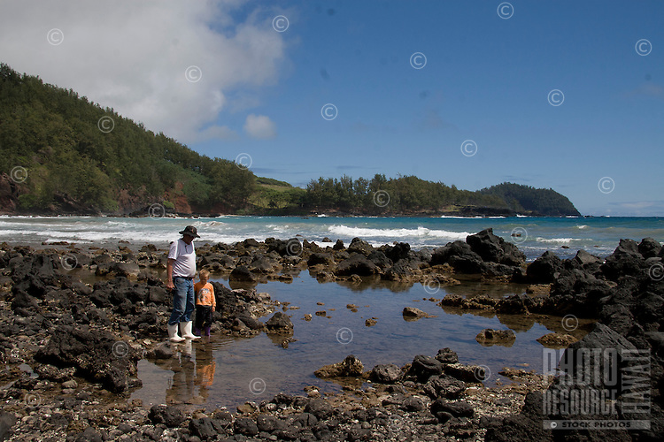 A father and son explore a tide pool at Koki Beach, just outside of Hana town, Maui.